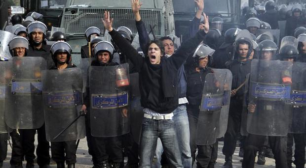 Egyptian anti-government protesters shout in front of riot police blocking a bridge in Cairo (AP)