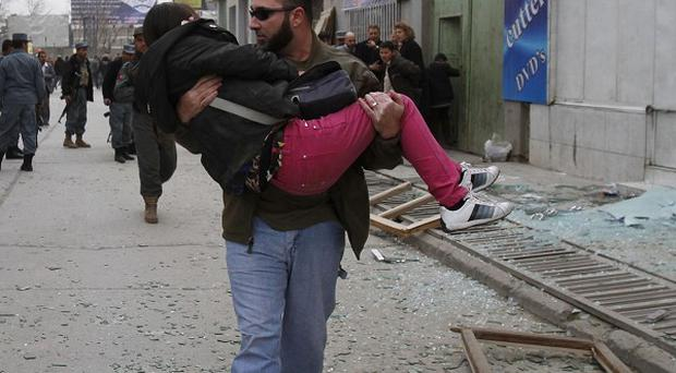 An injured woman is carried out of a supermarket following a suicide bombing in central Kabul (AP)