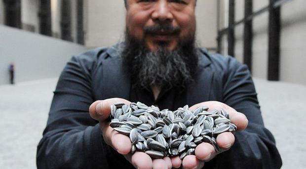 Ai Weiwei with his work 'Sunflower Seeds' at the Tate Modern, central London