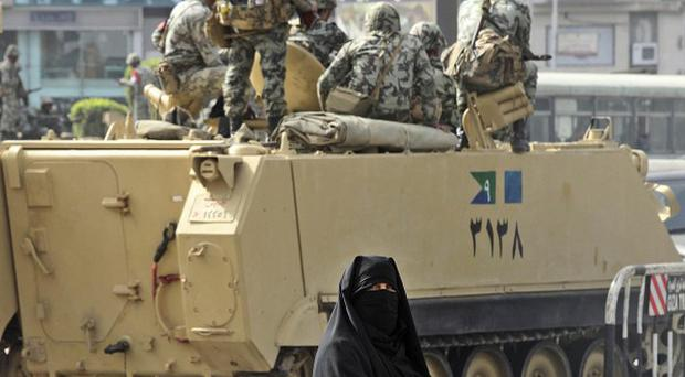 An Egyptian woman walks past an army personnel carrier in Cairo (AP)