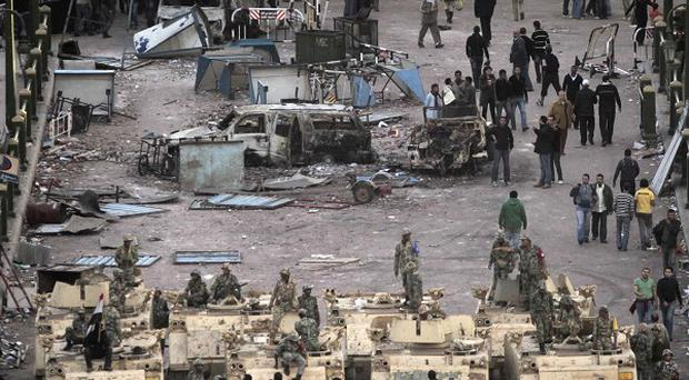 Egyptian army soldiers sit and stand atop their armoured personnel carriers as anti-government protesters gather in Tahrir square in Cairo (AP)