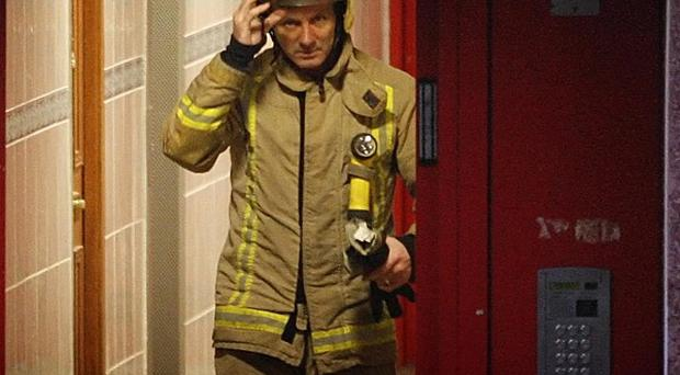 A fireman leaves a block of flats on Acre Road in Glasgow following the deaths of three people