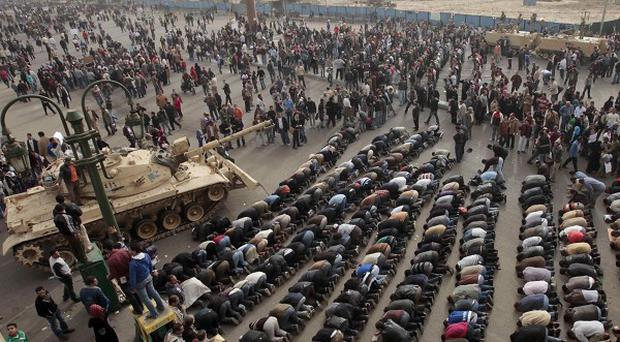 Egyptian anti-government protesters pray in front of an Egyptian army tank during a protest in Tahrir square in Cairo (AP)