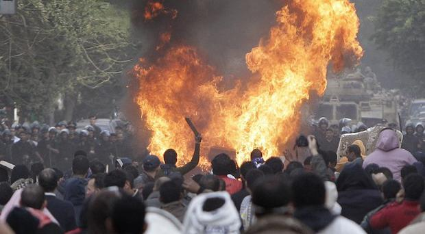Protesters throw firebombs at riot police in a street near Tahrir square in Cairo, Egypt (AP)