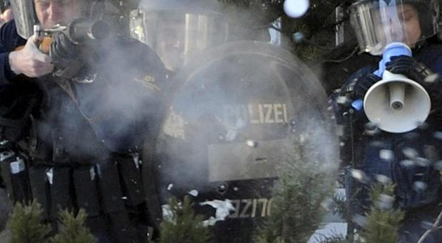 Police fire rubber bullets at protesters outside the meeting hall of the World Economic Forum in Davos (AP)