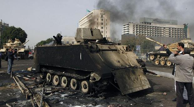 Egyptians photograph a burned-out army armoured personnel carrier in downtown Cairo (AP)