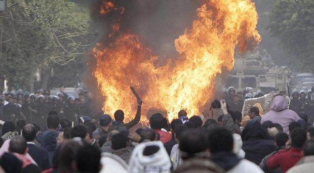 Protesters throw firebombs at riot police in a street near Tahrir Square in downtown Cairo (AP)
