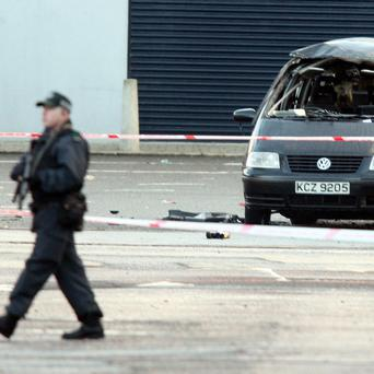 Armed police patrol near a car which was blown up by the Army in the Glandore area of north Belfast following a bomb alert