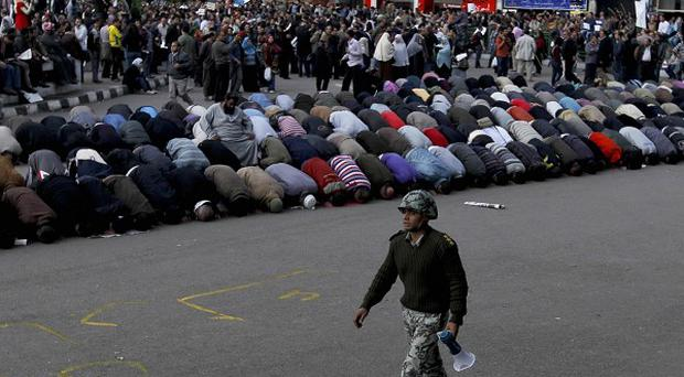An Egyptian soldier walks past anti-government protesters as they pray in Tahrir Square, Cairo (AP)