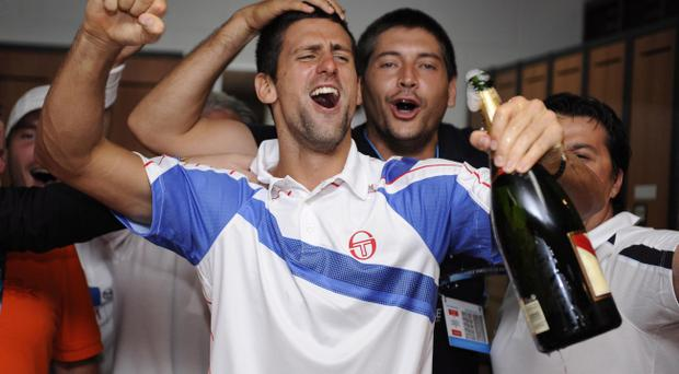 Serbia's Novak Djokovic celebrates with family and friends in the players locker room after defeating Britain's Andy Murray in the men's singles final at the Australian Open tennis championships in Melbourne, Australia, Sunday, Jan. 30, 2011.