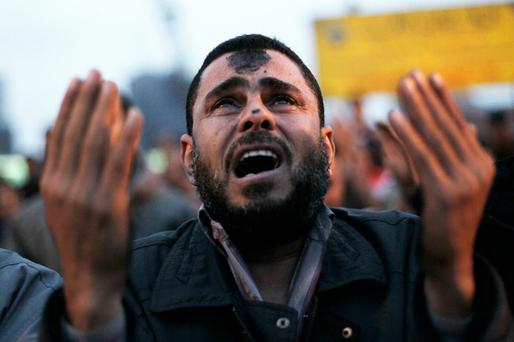 CAIRO, EGYPT - JANUARY 30: An anti-government protester cries during Islamic prayers in Tahrir Square at sundown January 30, 2011 in Cairo, Egypt. Cairo remained in a state of flux and marchers continued to protest in the streets and defy curfew, demanding the resignation of Egyptian president Hosni Mubarek. As President Mubarak struggles to regain control after five days of protests he has appointed Omar Suleiman as vice-president. The present death toll stands at 100 and up to 2,000 people are thought to have been injured during the clashes which started last Tuesday. Overnight it was reported that thousands of inmates from the Wadi Naturn prison had escaped and that Egyptians were forming vigilante groups in order to protect their homes. (Photo by Chris Hondros/Getty Images) *** BESTPIX ***