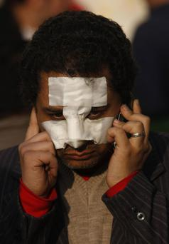 A man with a bandaged face uses a cellular phone during a demonstration in Cairo, Egypt, Sunday Jan. 30, 2011. Minutes before the start of a 4 p.m. curfew, at least two jets appeared and made multiple passes over downtown, including a central square where thousands of protesters were calling for the departure of President Hosni Mubarak. (AP Photo/Khalil Hamra)