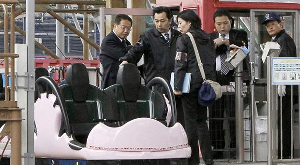 Police investigators examine a spinning roller coaster after a man fell to his death at the Tokyo Dome City Attractions