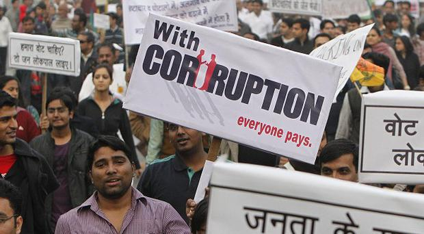 Demonstrators hold placards as they take part in a rally to protest against corruption and poor governance in New Delhi, India (AP)