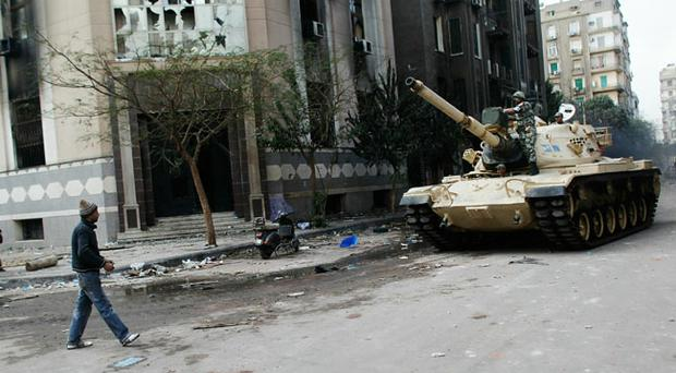 CAIRO, EGYPT - JANUARY 30: A man watches as an Egyptian Army tank approaches on January 30, 2011 in Cairo, Egypt. As President Mubarak struggles to regain control after five days of protests he has appointed Omar Suleiman as vice-president. The present death toll stands at 100 and up to 2,000 people are thought to have been injured during the clashes which started last Tuesday. Overnight it was reported that thousands of inmates from the Wadi Naturn prison had escaped and that Egyptians were forming vigilante groups in order to protect their homes after Police were nowhere to be seen on the streets. (Photo by Chris Hondros/Getty Images)