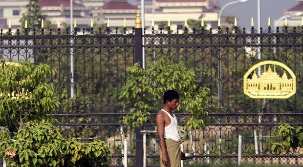 A man walks past the fence outside the parliament building in Naypyitaw, Burma (AP)