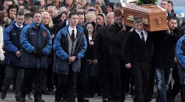 Press Eye Ltd -Northern Ireland - 31st January 2011. Funeral of 13-year-old Martin Rooney from Twinbrook in west Belfast who took his own life last week. Family and friends follow his coffin through the Twinbrook estate for Requiem Mass at St Luke's Church.