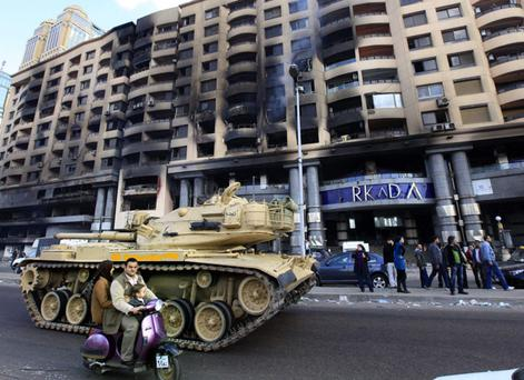 An Egyptian family riding a scooter pass by a fire-damaged shopping mall guarded by an army tank in Cairo, Egypt, Monday, Jan. 31, 2011. A coalition of opposition groups called for a million people to take to Cairo's streets Tuesday to ratchet up pressure for President Hosni Mubarak to leave. (AP Photo/Amr Nabil)