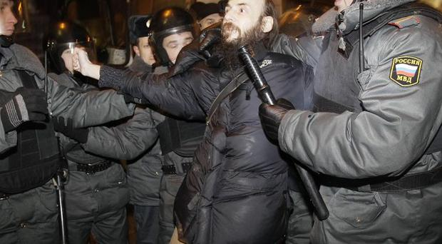 Russian police officers detain a protester during a rally in central Moscow (AP)