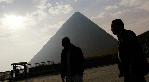 Two Egyptian men stand by the Pyramids in Cairo, Egypt