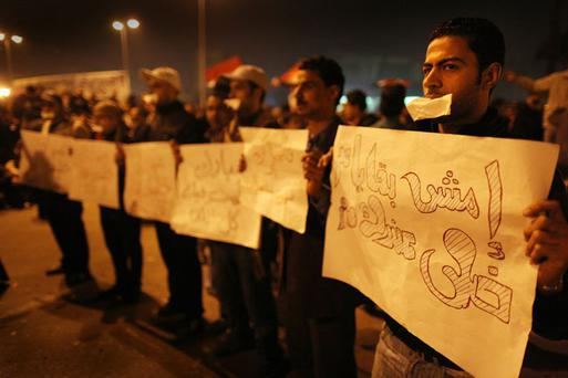CAIRO, EGYPT - FEBRUARY 01: Anti-government protestors continue to defy the curfew as they stand with placards in Tahrir Square on February 1, 2011 in Cairo, Egypt. Protests in Egypt continued with the largest gathering yet, with many tens of thousands assembling in central Cairo, demanding the ouster of Egyptian President Hosni Mubarek. The Egyptian army has said it will not fire on protestors as they gather in large numbers in central Cairo. (Photo by Peter Macdiarmid/Getty Images)