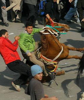Supporters of embattled Egyptian president Hosni Mubarak ride horses through the melee during a clash between pro- and anti-Mubarak protesters February 2, 2011 in Tahrir Square in Cairo, Egypt.