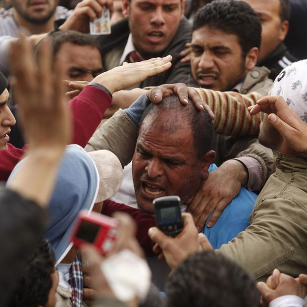 Demonstrators in Tahrir Square grab a man they suspect to be a supporter of Egypt's president Hosni Mubarak (AP)