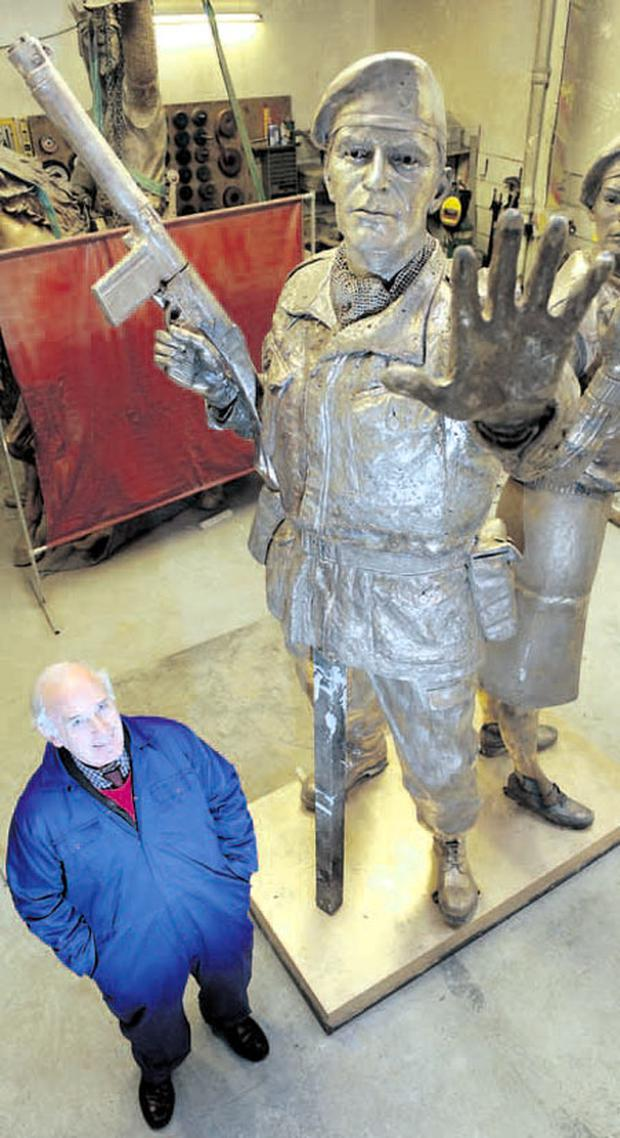 Sculptor John Sherlock with his creation, a 19ft high bronze statue commemorating all who served with the UDR