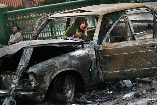 CAIRO, EGYPT - FEBRUARY 03: A woman protesting against the Egyptian government uses a burned out car to make a phone call February 3, 2011 in Tahrir Square in Cairo, Egypt. The stand off between anti- and pro-President Hosni Mubarak factions in Egypt's central square continuted February 3, after a day and night of violence in which hundreds were injured in clashes. (Photo by Chris Hondros/Getty Images)