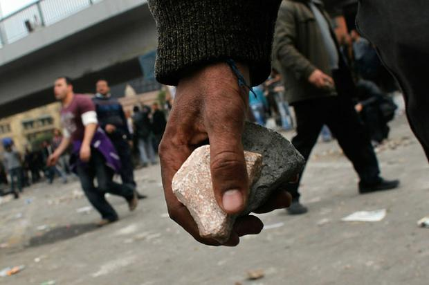 CAIRO, EGYPT - FEBRUARY 03: Anti-government protesters carry rocks to throw at pro-government supporters near a highway overpass on the edge of Tahrir Square the afternoon of February 3, 2011 in Cairo, Egypt. Clashes between anti- and pro-government factions in Egypt's central square continued February 3, with anti-government forces gaining more territory outside of Tahrir Square from Egyptians loyal to the government of Egyptian President Hosni Mubarak. (Photo by Chris Hondros/Getty Images)