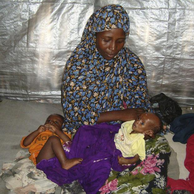 A woman with one of her children awaiting treatment at the Hawa Abdi hospital in Afgoye, Somalia (AP)