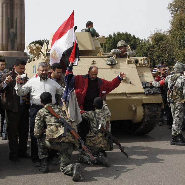 Egyptian soldiers search anti-government protesters in Cairo's Tahrir Square (AP)
