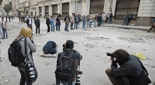 Photographers take pictures of an anti-government protester praying in Tahrir Square (AP)