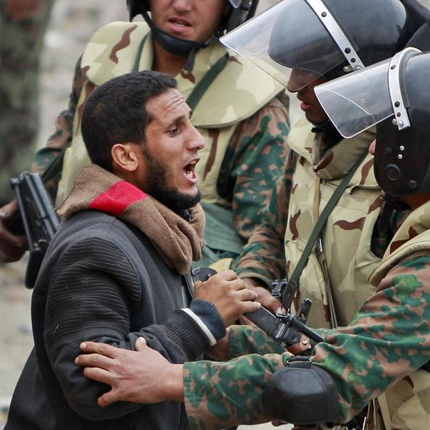 An anti-government protester pleads with a soldier not to remove opposition barricades (AP)