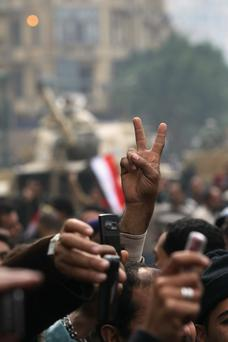 CAIRO, EGYPT - FEBRUARY 07: An anti-government demonstrator shows the victory sign as others shoot video on their celular phones in Tahrir Square on February 7, 2011 in Cairo, Egypt. Almost two weeks since the uprising began, thousands of protesters continue to occupy the square, demanding the resignation of President Hosni Mubarak. (Photo by John Moore/Getty Images)