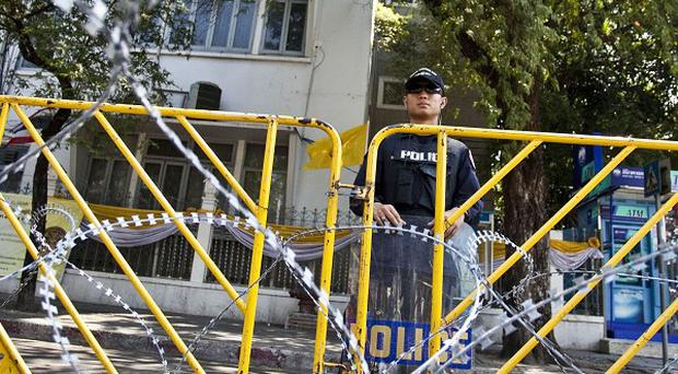 Police stand guard behind barricades near Government House in Bangkok, Thailand (AP)