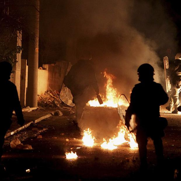 Riot police officers walk among fire from petrol bombs thrown by protesters in Keratea, 30 miles south-east of Athens (AP)