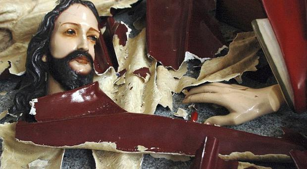 A statue of Jesus Christ is left smashed on the floor in Temanggung, Indonesia (AP)