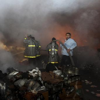 Palestinian firefighters try to extinguish a fire at a burning medicine warehouse in Gaza City (AP)