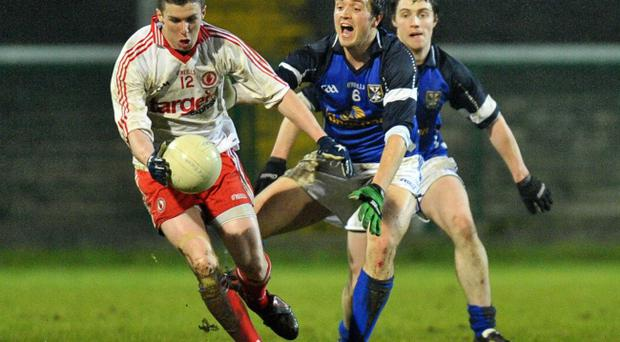 Tyrone's Patrick McNeice is challenged by John McCutcheon at Brewster Park last night