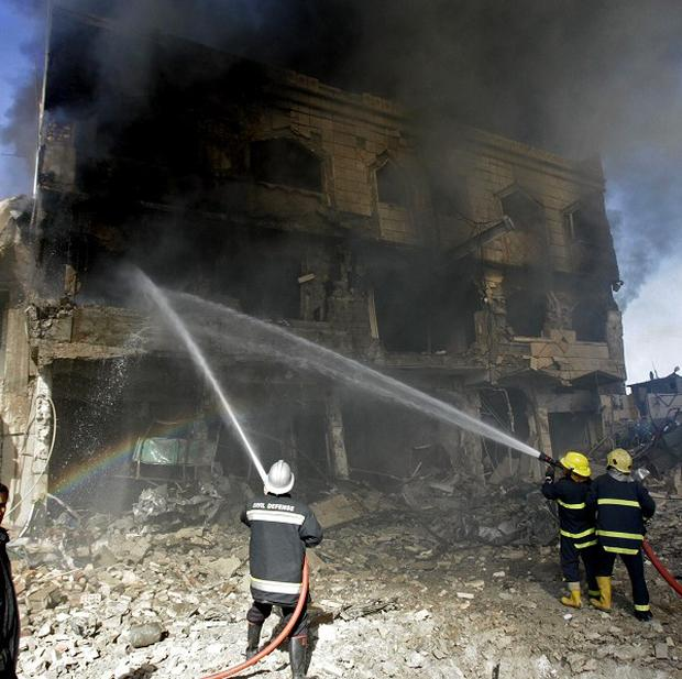 Iraqi firefighters extinguish a fire in a destroyed building after a car bomb attack in Kirkuk (AP)