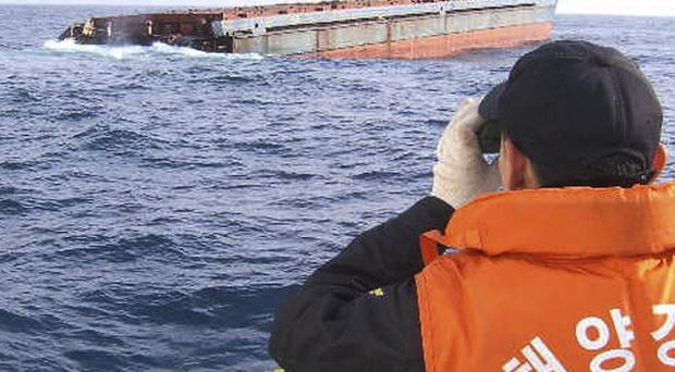A member of the coastguard searches for survivors after ships collided off South Korea (AP)
