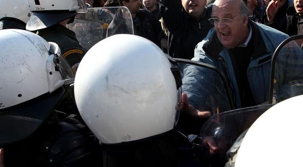 Riot police confront protesting doctors on strike outside the Greek Parliament, in Athens (AP)