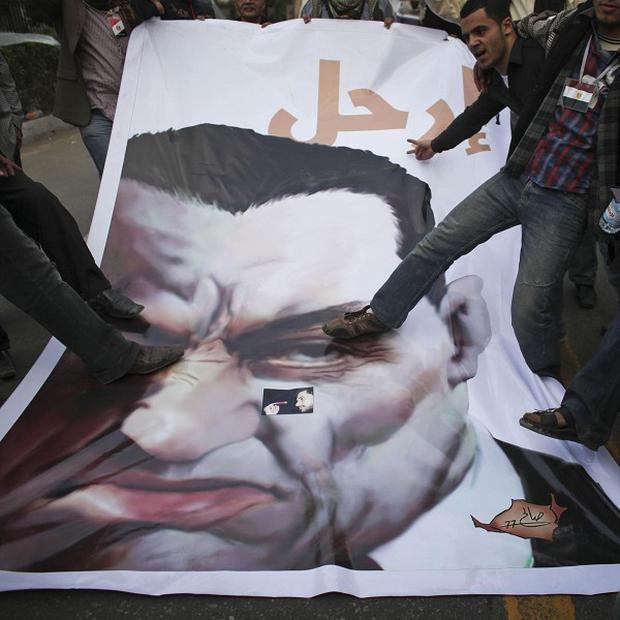 Anti-government protesters stamp on a poster of Egyptian president Hosni Mubarak, as fears grow for a Briton missing in Cairo