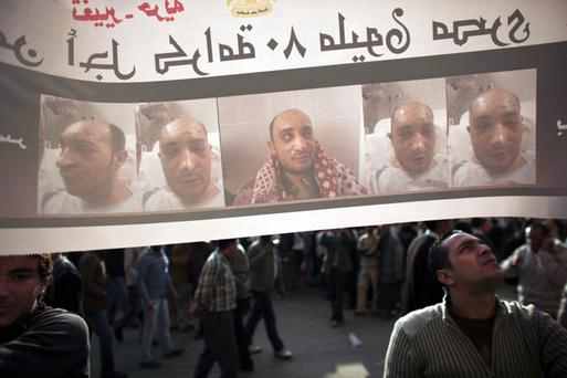 An anti-government protester looks at a poster of a man who was injured during clashes with police in Tahrir Square