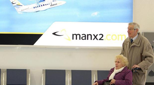People passing a Manx2 poster at George Best Belfast City Airport