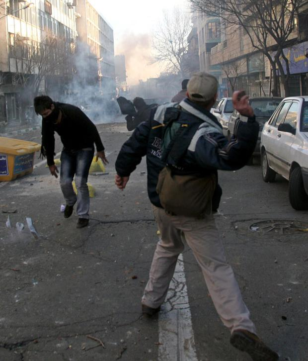 Iranian protestors throwing stones at anti-riot police officers, during an anti-government protest in Tehran, Iran, Monday, Feb. 14, 2011
