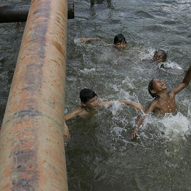 Children play in a river where oil pipes run above the surface in Ecuador's Sucumbios province (AP)