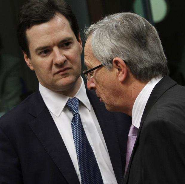Jean Claude Juncker speaks with George Osborne during a meeting of EU finance ministers in Brussels (AP)