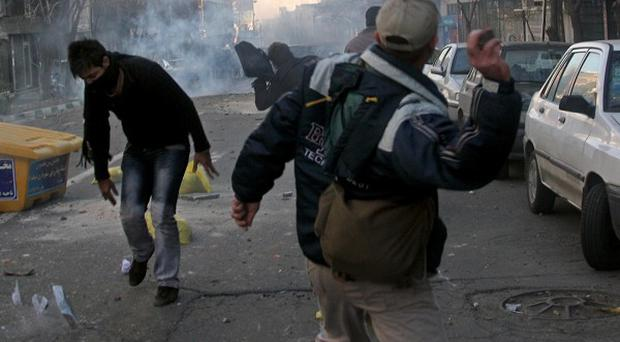 Iranians throw stones at anti-riot police officers during a protest in Tehran
